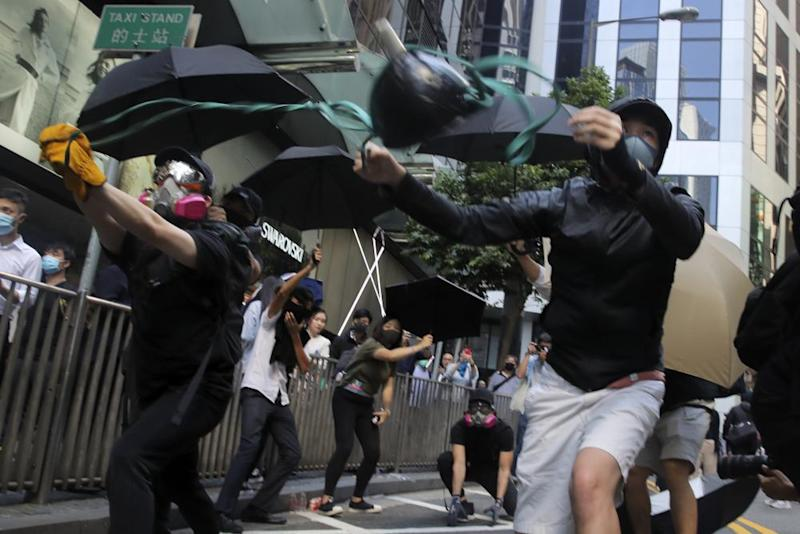 Protesters use a catapult to launch a milk carton at riot police during protests in the Central district of Hong Kong on Monday.