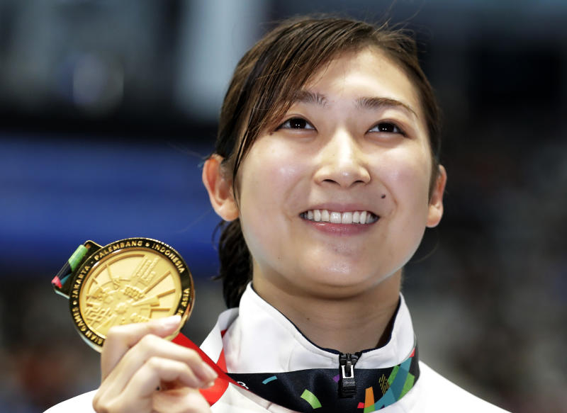 FILE - In this Aug. 24, 2018, file photo, Japan's Rikako Ikee holds up her gold medal after winning the women's 50m freestyle final during the swimming competition at the 18th Asian Games in Jakarta, Indonesia. Ikee, the favorite for the 100-meter butterfly for the 2020 Tokyo Olympics, has been diagnosed with leukemia. Ikee said on her verified Twitter account Tuesday, Feb. 12, 2019, her illness surfaced when she got tests after returning from Australia not feeling well. (AP Photo/Lee Jin-man, File)