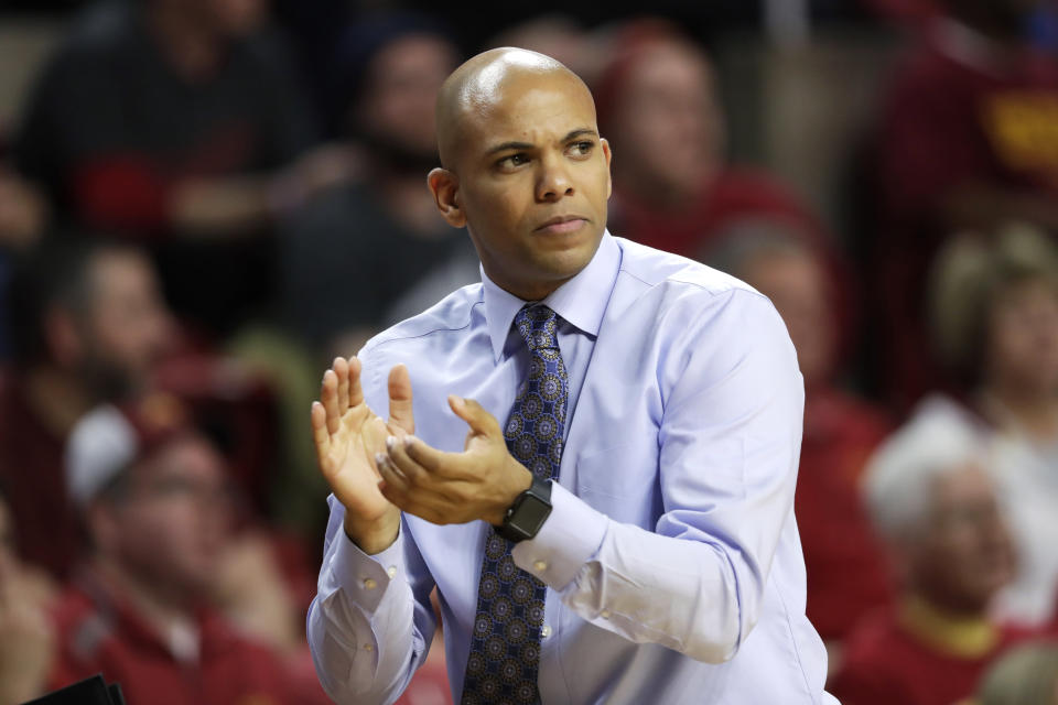 FILE - In this Monday, Nov. 14, 2016 file photo, Then-Mount St. Mary's head coach Jamion Christian applauds his team during the first half of an NCAA college basketball game against Iowa State in Ames, Iowa. For all the stops and starts endured by men's and women's college basketball teams because of the pandemic, more than 80% of scheduled conference games were played this season, according to research by The Associated Press. The season was nonetheless a grind for most teams and none had it harder than the George Washington men and UC Davis women. (AP Photo/Charlie Neibergall, File)