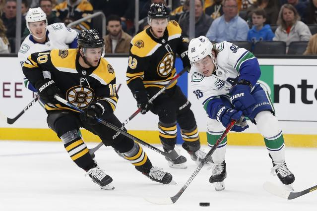 Boston Bruins' Anders Bjork (10) and Vancouver Canucks' Adam Gaudette (88) battle for the puck during the first period of an NHL hockey game in Boston, Tuesday, Feb. 4, 2020. (AP Photo/Michael Dwyer)
