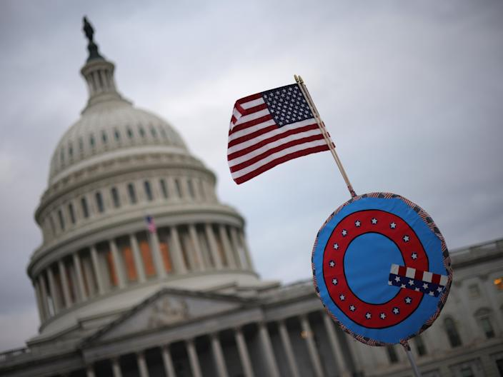 Trump supporters fly a US flag with a symbol denoting QAnon as they gather outside the US Capitol on 6 January (Win McNamee/Getty Images)