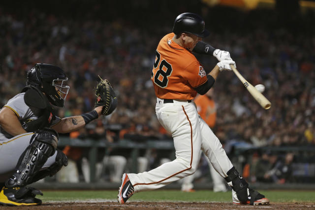 FILE - In this Aug. 10, 2018, file photo, San Francisco Giants' Buster Posey hits a two-run single off Pittsburgh Pirates starting pitcher Clay Holmes during the third inning of a baseball game, in San Francisco. Working out his lower body with a 15-pound dumbbell in his left hand he leaned forward to do a one-legged dead lift. Posey immediately felt the muscles in his right buttocks being used exactly the way they should. Posey certainly plans to be a full participant from Day 1 of spring training, pulling on the catchers gear and squatting behind the plate for bullpens. (AP Photo/Eric Risberg, File)