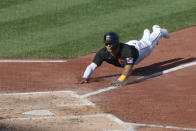 Pittsburgh Pirates' Phillip Evans, left, dives for home plate to score on a wild pitch by Detroit Tigers starter Ivan Nova to Pirates' Jacob Stallings in the fourth inning of a baseball game Saturday, Aug. 8, 2020, in Pittsburgh. (AP Photo/Keith Srakocic)