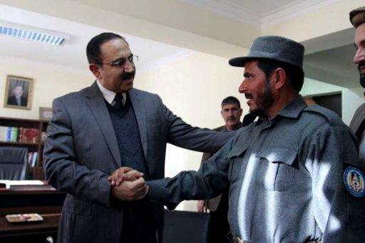 Afghanistan's Interior Minister Mujtaba Patang (left) speaks with a police officer in Kabul, on December 25, 2012