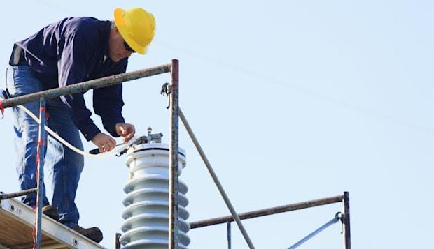 Power engineer performing maintenance on fluid filled high voltage insulator