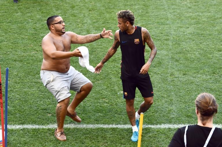 A fan storms the field to hug Barcelona's Brazilian forward Neymar during a training session in Harrison, New Jersey
