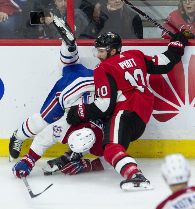 Ottawa Senators left wing Tom Pyatt battles with Montreal Canadiens defenseman Xavier Ouellet along the boards during the first period of an NHL game in Ottawa, Ontario, Saturday, Oct. 20, 2018. (Adrian Wyld/The Canadian Press via AP)