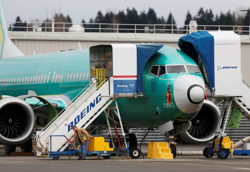 An employee works near a Boeing 737 Max aircraft at Boeing's 737 Max production facility in Renton