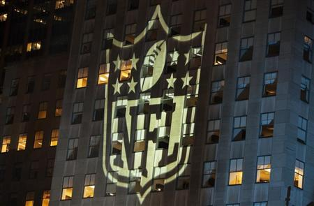 A man stands at a window lit by the NFL logo in New York