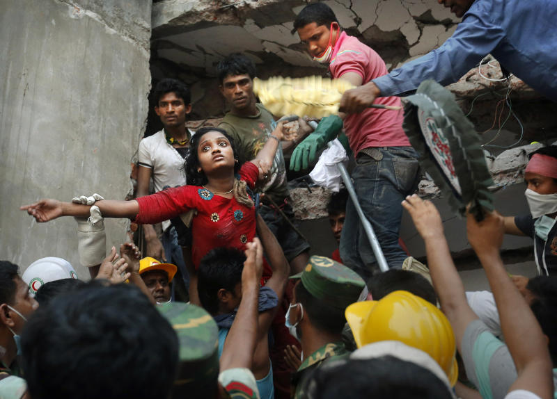 FILE - A Bangladeshi woman survivor is lifted out of the rubble by rescuers at the site of a building that collapsed Wednesday in Savar, near Dhaka, Bangladesh, Thursday, April 25, 2013. This image was chosen by the Associated Press as one of the top 10 news photos representing the top stories of 2013. (AP Photo/Kevin Frayer, File)