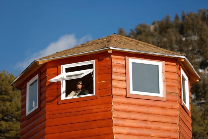 Assistant manager of a Fortitude Ranch camp stands armed in a lookout tower at a survival camp