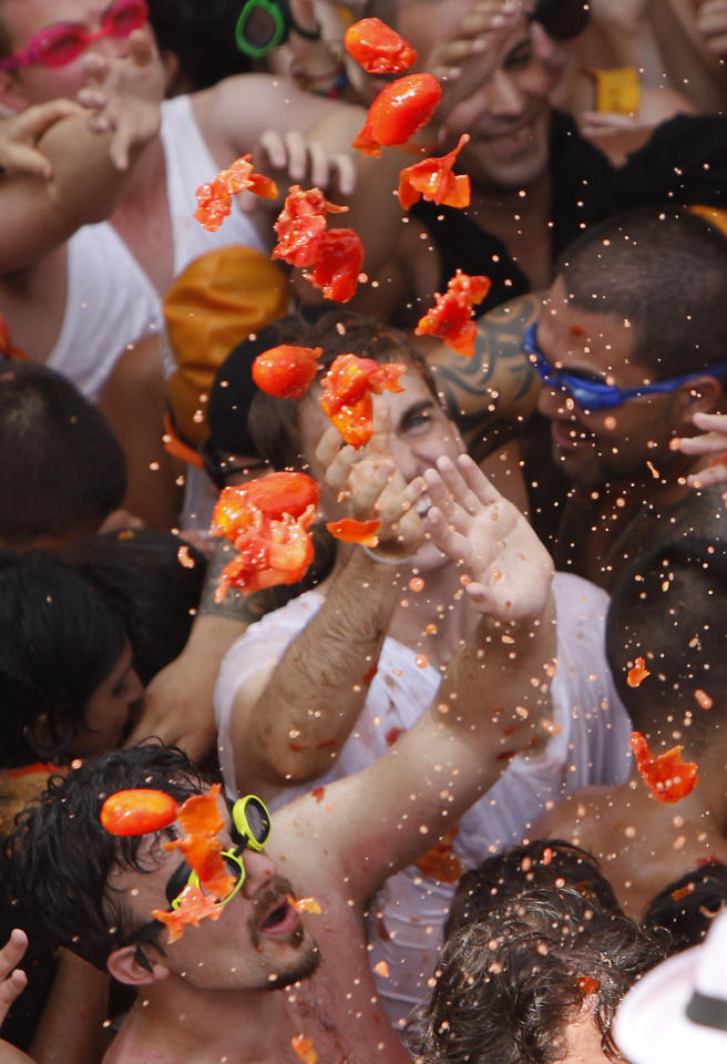 """Revelers throw tomatoes during the annual """"Tomatina"""" tomato fight fiesta in the village of Bunol, near Valencia, Spain, Wednesday, Aug. 31, 2011. Bunol's town hall estimated more than 40,000 people, some from as far away as Japan and Australia, took up arms Wednesday and pelted each other with 120 tons of ripe tomatoes in the yearly food fight known as the 'Tomatina' now in its 66th year. (AP Photo/Alberto Saiz)"""