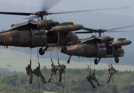 Japanese Ground Self-Defense Force soldiers rappel from UH-60 Black Hawk helicopters during an annual training session near Mount Fuji at Higashifuji training field in Gotemba