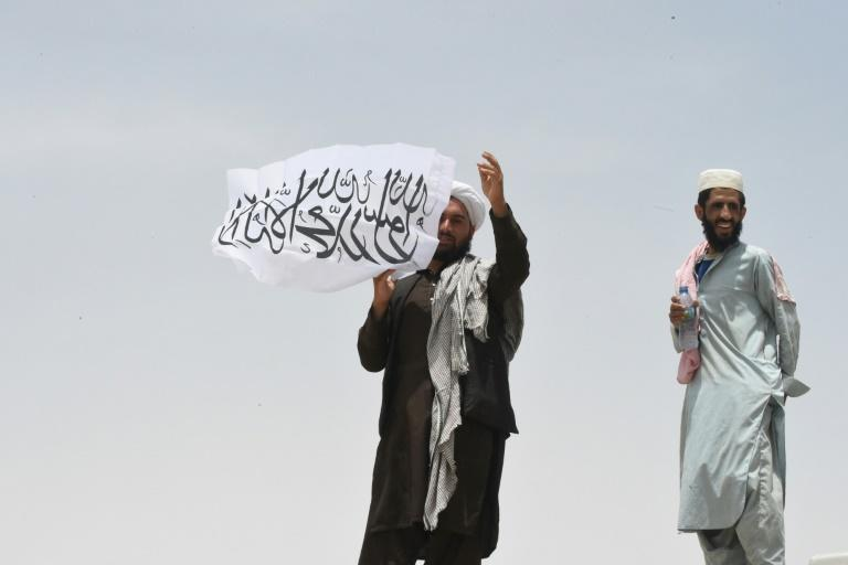 A man standing on Afghanistan's side of the border holds a Taliban flag as people walk towards a border crossing point in Pakistan