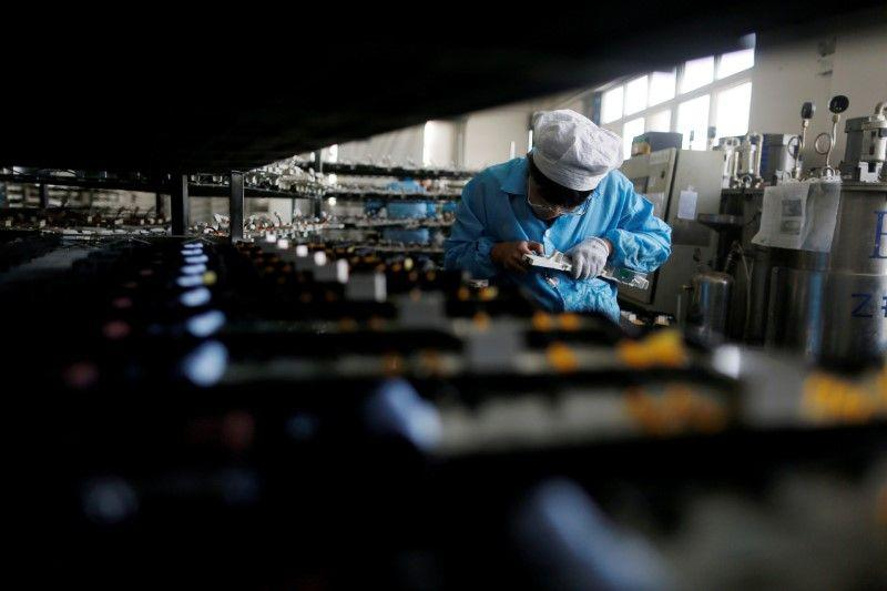 A labourer works inside an electronics factory in Qingdao, Shandong province in China January 29, 2018. ― Reuters pic