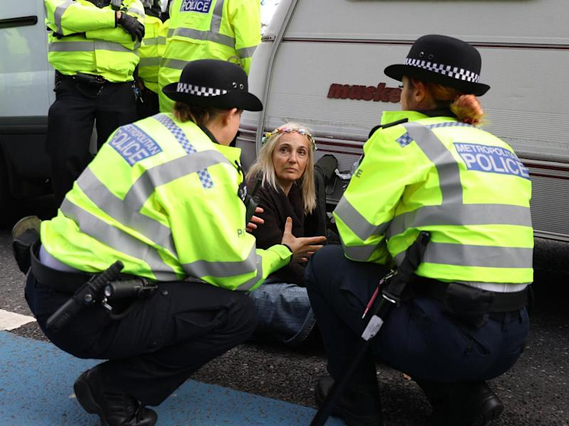 Police speak to an Extinction Rebellion protester outside MI5 Headquarters on Millbank in London: PA