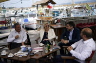 FILE - In this June 17, 2021, file photo, far-right leader Marine le Pen, center, and local candidate Thierry Mariani, left, enjoy a drink at a cafe terrace in Six-Fours-les-Plages, southern France. Le Pen's once-ascendant far-right party is struggling ahead of runoff elections for France's regional leadership. Its best chance of victory is Mariani, a European lawmaker who meets regularly with Syrian dictator Bashar al-Assad and celebrated Russia's annexation of Crimea. (AP Photo/Daniel Cole, File)