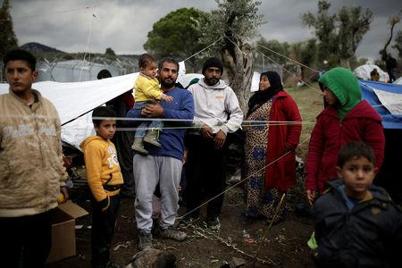 Syrian refugee Bashar Wakaa (3rd L) and his family stand in front of their tents at a makeshift camp for refugees and migrants next to the Moria camp on the island of Lesbos, Greece, November 30, 2017. REUTERS/Alkis Konstantinidis