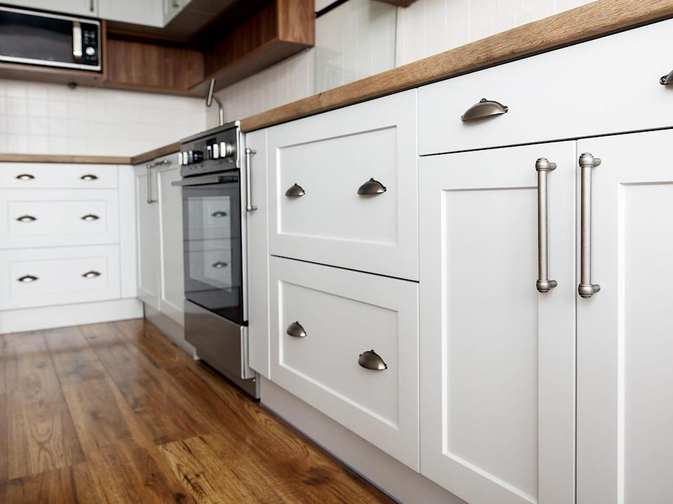 Stylish light grey handles on cabinets close-up, kitchen interior with modern furniture and stainless steel appliances, kitchen design in scandinavian style