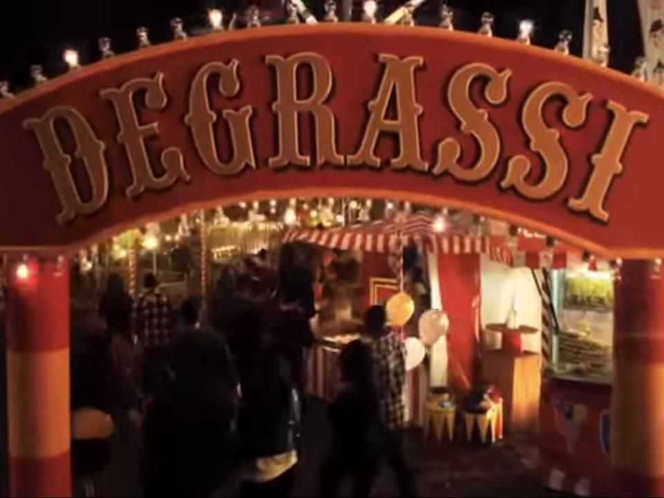red degrassi sign at the entrance to a carnival, shark in the water promo video