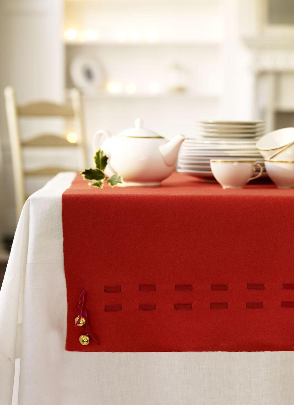 <p>Give pricey table linens a run for their money with this woven ribboned beauty. Start with non-fraying fabric, like felt or heavy wool, that's sized as a runner for your table. Four inches up from the runner's bottom and 3 inches in from the edge, cut a 1⁄2-inch pair of parallel vertical slits 2 inches apart. Make another pair of vertical cuts 3 inches away from the first set of slits. Repeat along the width of the runner. Thread a 1⁄2-inch velvet ribbon through the slits. Punch a hole through fabric to insert the end of the ribbon. Tie bells onto the end of the ribbon for a jingly finish.<br> </p>
