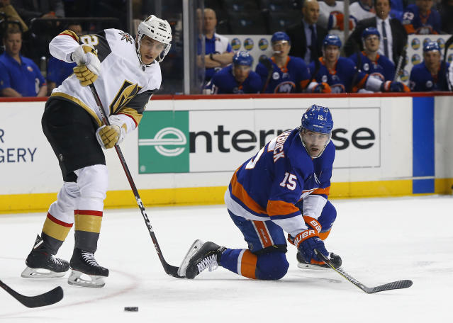 New York Islanders right wing Cal Clutterbuck (15) plays the puck against Vegas Golden Knights left wing Tomas Nosek during the second period of an NHL hockey game, Wednesday, Dec.12, 2018, in New York. (AP Photo/Noah K. Murray)