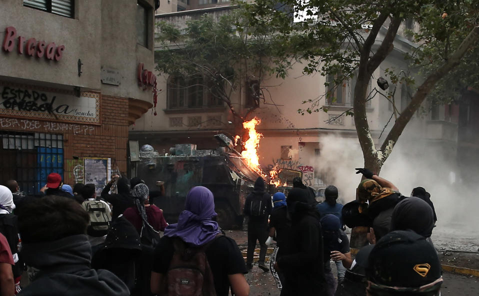 Anti-government protesters throw petrol bombs at a police truck in Santiago, Chile, Friday, Nov. 8, 2019. Chile's president on Thursday announced measures to increase security and toughen sanctions for vandalism following three weeks of protests that have left at least 20 dead. (AP Photo/Luis Hidalgo)