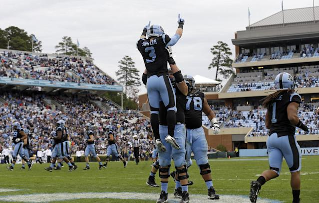 North Carolina's James Hurst hoists Ryan Switzer (3) after Switzer's touchdown against Old Dominion during the first half of an NCAA college football game in Chapel Hill, N.C., Saturday, Nov. 23, 2013. North Carolina won 80-20. (AP Photo/Gerry Broome)