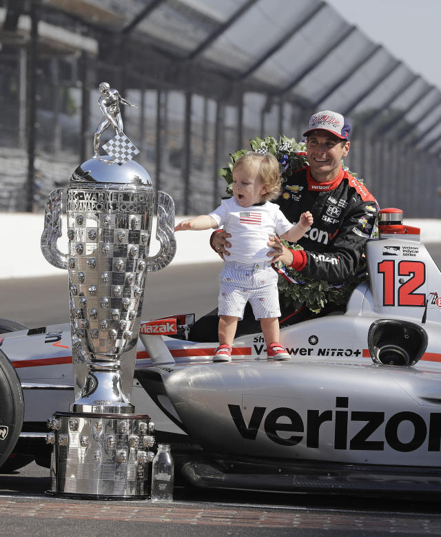 Indianapolis 500 champion Will Power, of Australia, holds for his son, Beau, as he poses with the Borg-Warner Trophy during the traditional winners photo session on the start/finish line at the Indianapolis Motor Speedway, Monday, May 28, 2018, in Indianapolis. (AP Photo/Darron Cummings)