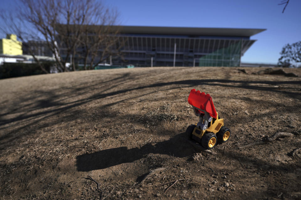 A leftover toy bulldoze is seen near the Tokyo Aquatics Center, one of the venues of Tokyo 2020 Olympic and Paralympic games, in Tokyo Wednesday, Jan. 20, 2021. The postponed Tokyo Olympics are to open in just six months. Local organizers and the International Olympic Committee say they will go ahead on July 23. But it's still unclear how this will happen with virus cases surging in Tokyo and elsewhere around the globe. (AP Photo/Eugene Hoshiko)
