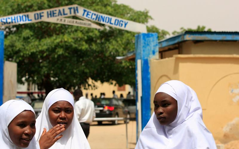 Young women stand in front of a school in Maiduguri, Nigeria - AP