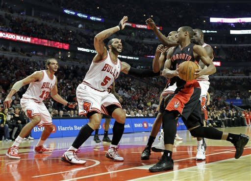 Toronto Raptors guard DeMar DeRozan (10) drives to the basket as Chicago Bulls forward Carlos Boozer (5) guards and Joakim Noah (13) looks on during the first quarter of an NBA basketball game in Chicago on Saturday, Jan. 14, 2012. (AP Photo/Nam Y. Huh)