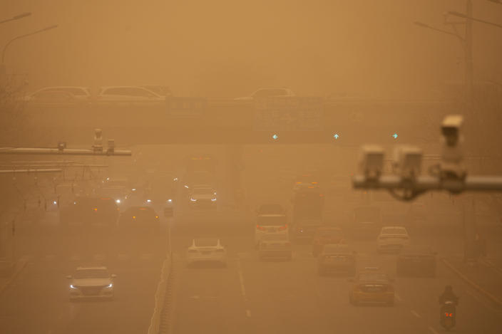 Cars are driven along a street amid a sandstorm during the morning rush hour in Beijing, Monday, March 15, 2021. The sandstorm brought a tinted haze to Beijing's skies and sent air quality indices soaring on Monday. (AP Photo/Mark Schiefelbein)