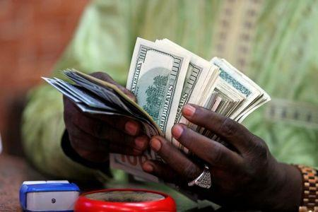 A bureau de change operator counts U.S. currency notes in Abuja