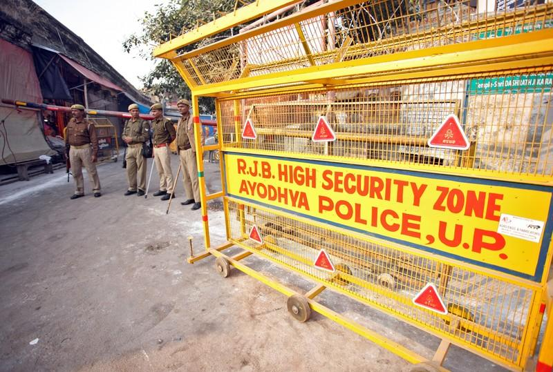 Policemen stand guard next to a security barricade on a street in Ayodhya