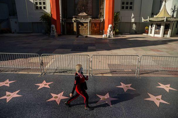 PHOTO: A pedestrian walks past the closed TCL Chinese Theatre, a normally packed tourist destination on Hollywood Boulevard in Los Angeles, Tuesday, March 24, 2020. (Damian Dovarganes/AP)