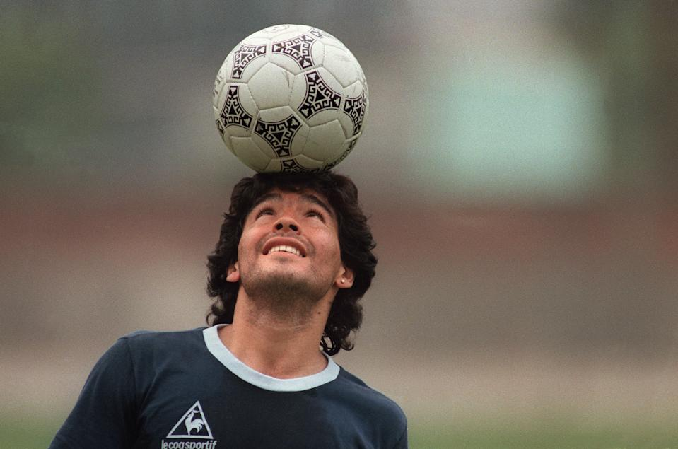 Diego Maradona balances a soccer ball on his head as he walks off the practice field following the Argentina national team practice session ahead of the 1986 World Cup. (PHOTO: Jorge Duran/AFP via Getty Images)