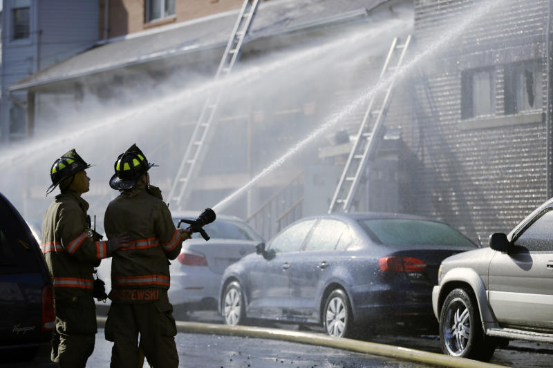 Firefighters battle a multialarm fire at a building in Harrison, N.J., Sunday, March 10, 2013. The blaze gutted a two-story building with a restaurant on the ground floor and then spread to a two-story residential building. There are reports of at least four firefighters sustaining minor injuries. (AP Photo/Mel Evans)