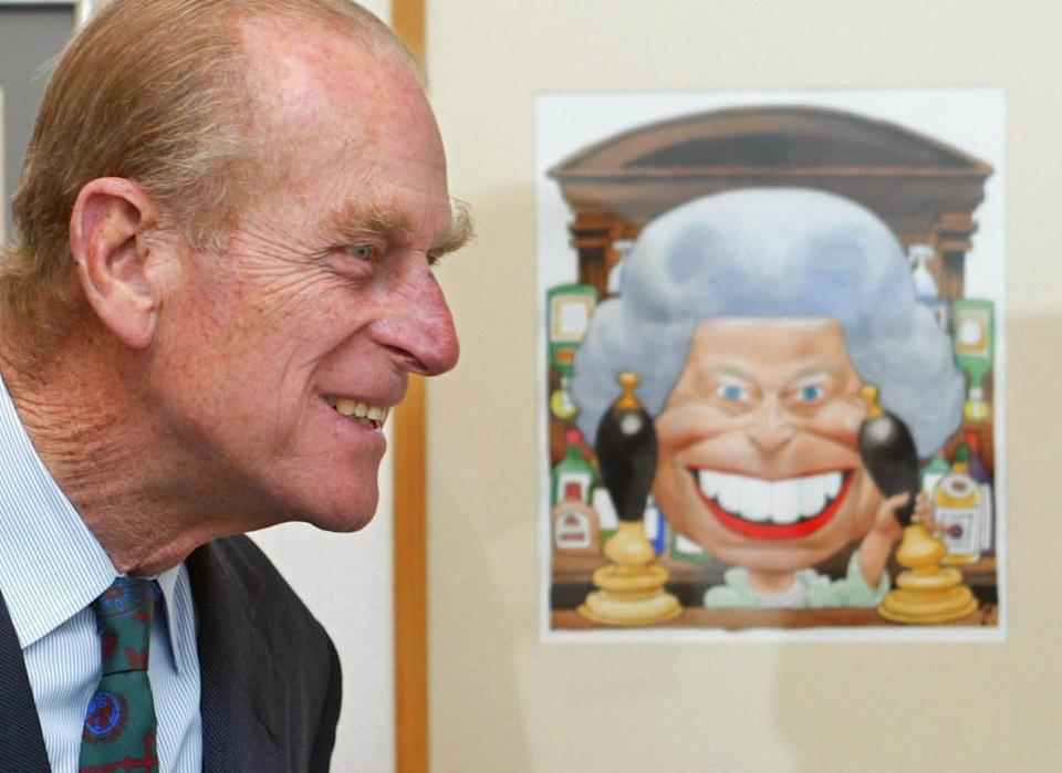 <p>Prince Philip looks at a cartoon of Queen Elizabeth II standing behind the bar in the Old Vic pub from TV show Eastenders drawn by Trogg for the Golden Jubille. The Duke was on a visit to the Cartoon Art Trust's Kings and Queens exhibition at the Mall Galleries, London, of which he is a patron. (PA/PA Archive/PA Images) </p>