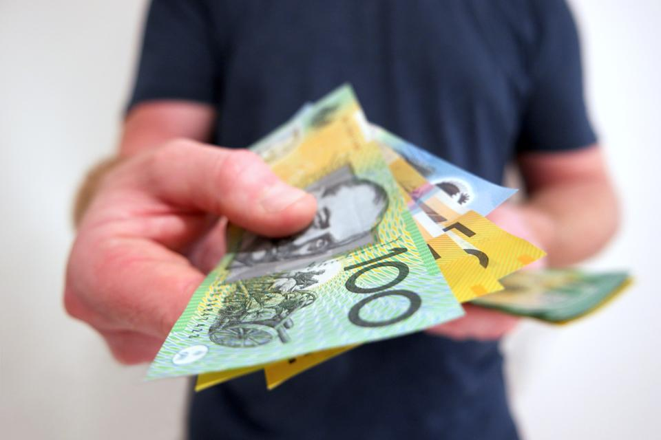 A man handing out Australian dollar bills. A picture that describes buying, paying, handing out money, or showing money.