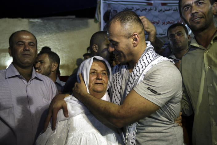 Palestinian released prisoner Burhan Sbeih kisses his mother at his home in the West Bank village of Kofr Raei near Jenin city after his release, Wednesday, Aug. 14, 2013. Israel released 26 Palestinian inmates, including many convicted in grisly killings, on the eve of long-stalled Mideast peace talks, angering families of those slain by the prisoners, who were welcomed as heroes in the West Bank and Gaza. (AP Photo/Mohammed Ballas)