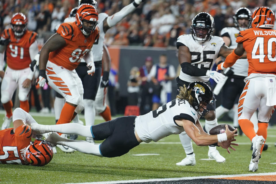 Jacksonville Jaguars quarterback Trevor Lawrence (16) dives in for touchdown while being tackled by Cincinnati Bengals' Logan Wilson (55) during the first half of an NFL football game, Thursday, Sept. 30, 2021, in Cincinnati. (AP Photo/Michael Conroy)