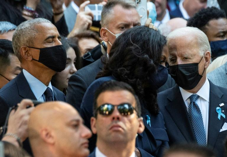 US President Joe Biden (R), with former President Barack Obama (L), speaks with former First Lady Michelle Obama as they attend the ceremony at the National 9/11 Memorial marking the 20th anniversary of the 9/11 attacks on the World Trade Center, in New York, on September 11, 2021 (AFP/Jim WATSON)