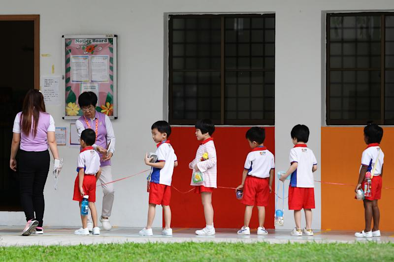 Children attending PAP Community Foundation (PCF) Sparkletots preschool here are seen praticising safe distancing on 30 March, 2020. (PHOTO: Getty Images)