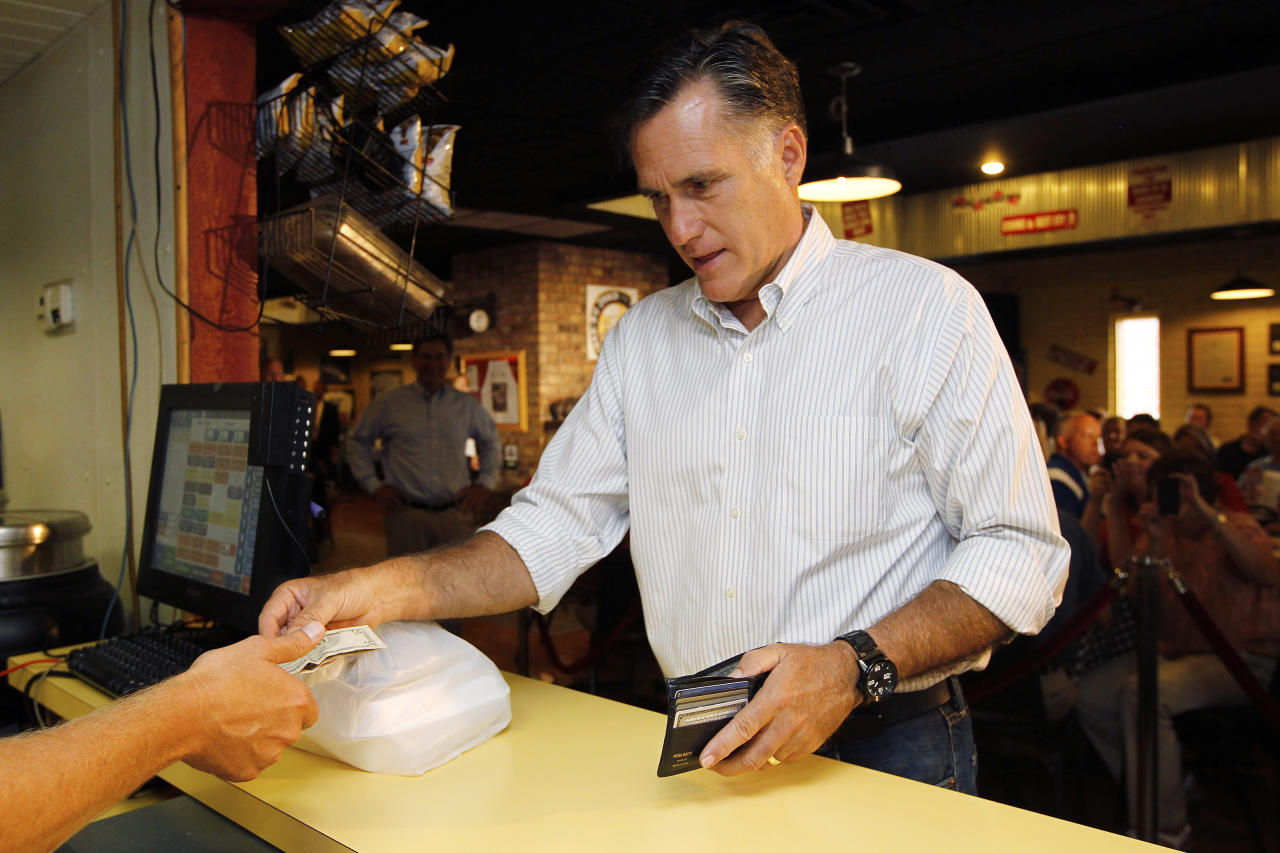 Republican presidential candidate and former Massachusetts Gov. Mitt Romney pays for a pulled chicken sandwich as he campaigns at Stepto's BBQ Shack in Evansville, Ind., Saturday, Aug. 4, 2012. (AP Photo/Charles Dharapak)