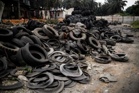 Bales of tyres from Australia and New Zealand are dumped at a compound next to the living quarters of the workers at a tyre pyrolysis plant in Kulai