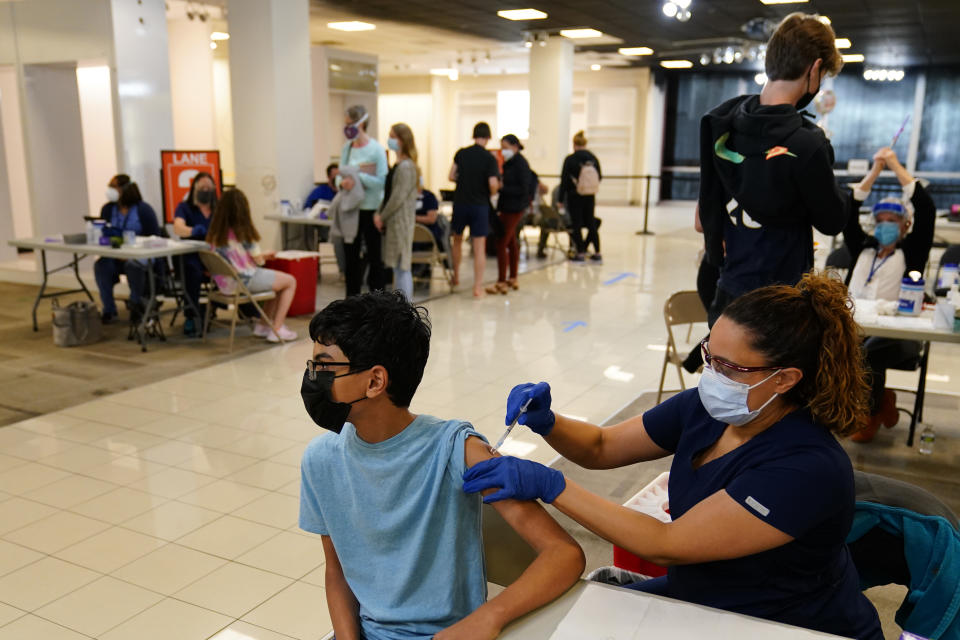 Manaf Albarakati, 14, of Narberth, Pa., receives a Pfizer COVID-19 vaccination from registered nurse Alicia Jimenez at a Montgomery County, Pa., Office of Public Health vaccination clinic at the King of Prussia Mall, Tuesday, May 11, 2021, in King of Prussia, Pa.. (AP Photo/Matt Slocum)