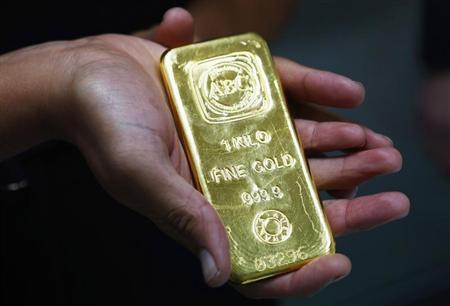 A woman holds a one-kilogram gold bar at the headquarters of the Australian Bullion Company in Sydney