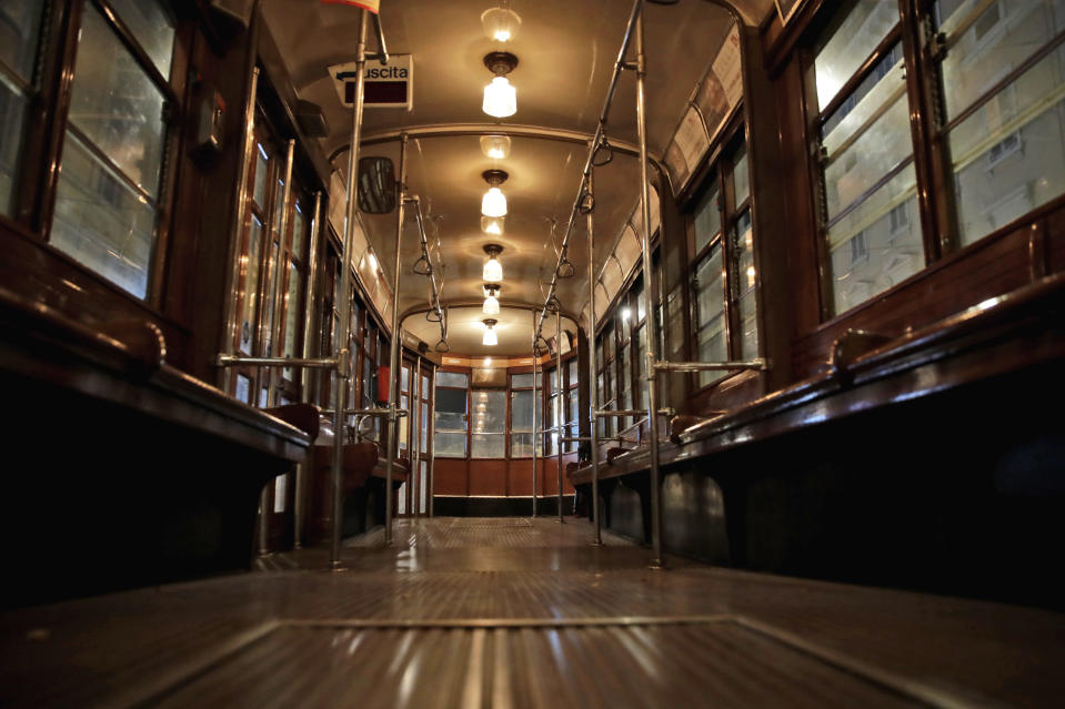 An empty tram street car runs in Milan, northern Italy, early Sunday, Oct. 25, 2020. Since the 11 p.m.-5 a.m. curfew took effect last Thursday, people can only move around during those hours for reasons of work, health or necessity. (AP Photo/Luca Bruno)