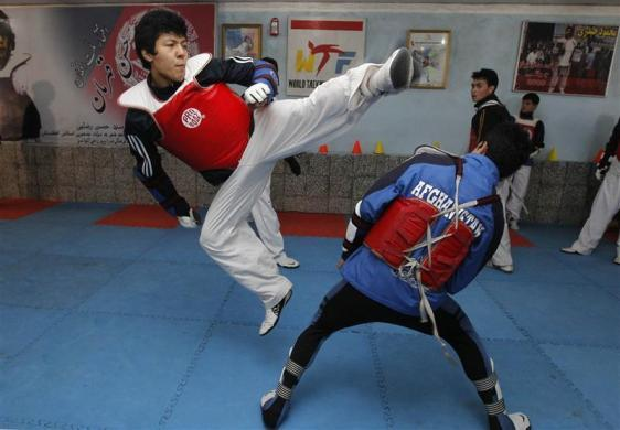 Rohullah Nikpai (L) trains inside a tae kwon do club in Kabul February 15, 2012. In a country wrenched by decades of war, perhaps it is no surprise that three Afghan athletes going to the London summer Olympic, a tae kwon do male duo including Beijing bronze medallist Nikpai, and teenage female boxer Sadaf Rahimi, followed fighting sports.